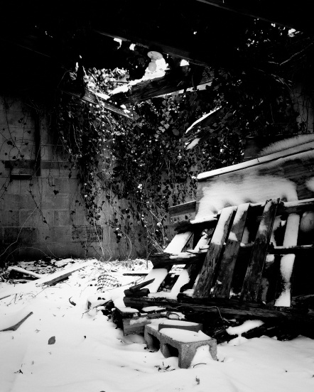 A black and white photo of a crumbling structure with snow falling through the broken roof