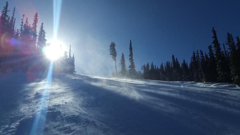 Sunshine and show blowing on a ski run