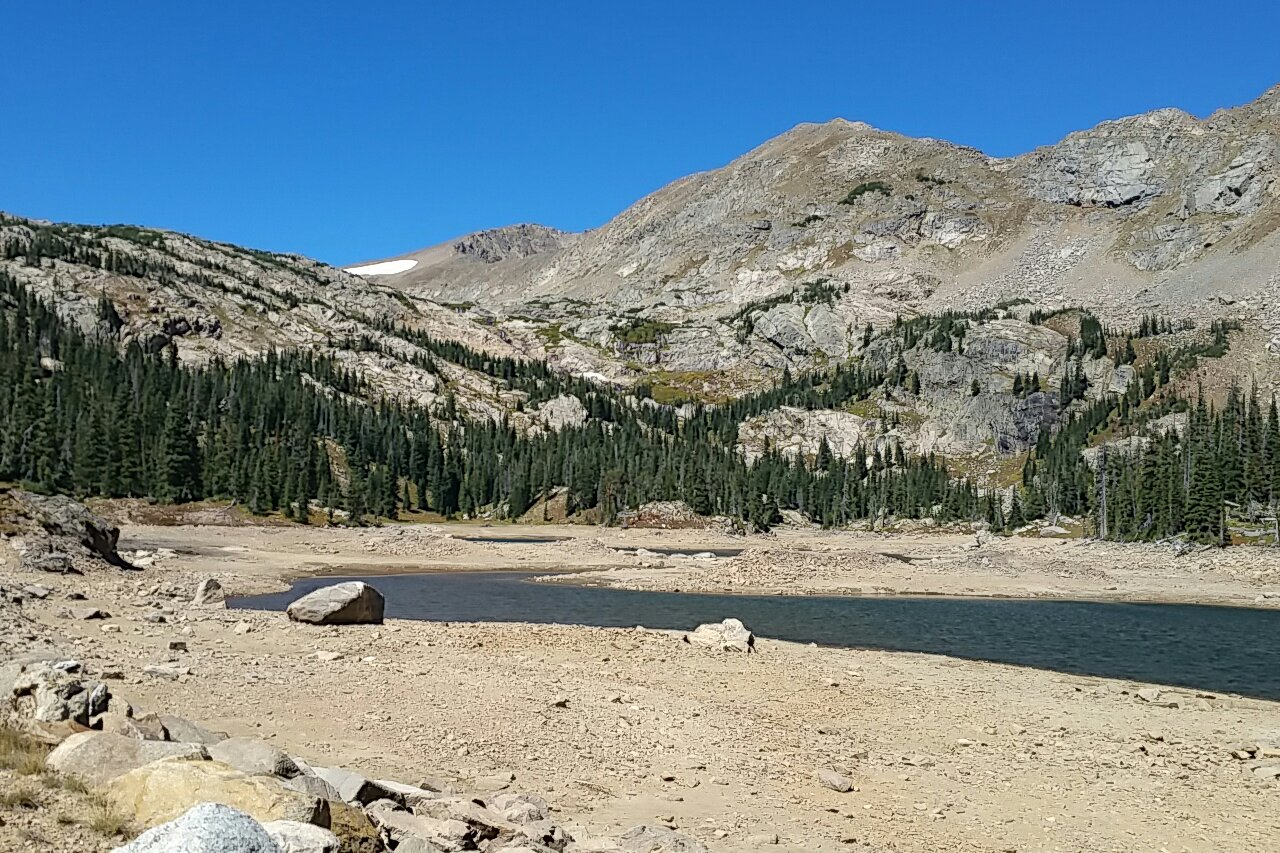 Jasper Lake, a high alpine lake in the Indian Peaks Wilderness of Colorado, during a period of low water.