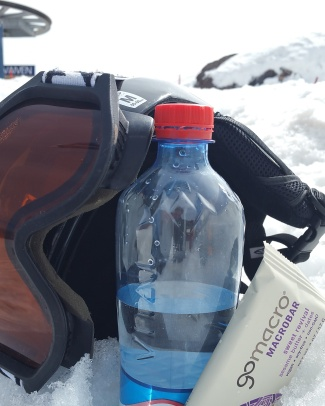 A ski helmet and goggles with a water bottle and snack.