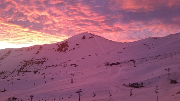 A view of El Colorado from Valle Nevado during a stunning pink sunset.